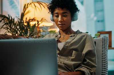 Buy stock photo Shot of a young woman wearing headphones while sitting at home with her laptop