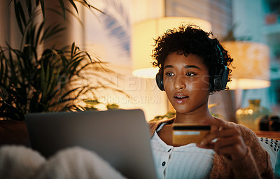 Buy stock photo Cropped shot of a young woman holding her credit card while using her laptop at night