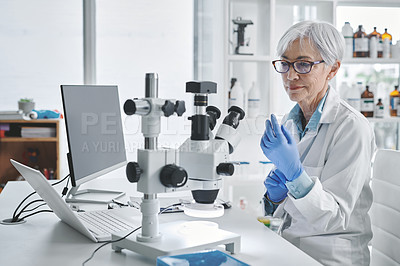 Buy stock photo Shot of a mature scientist wearing protective gloves while working in a lab