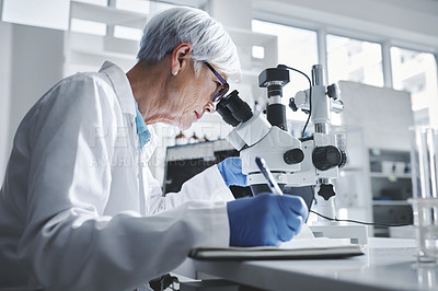 Buy stock photo Shot of a mature scientist writing notes while using a microscope in a lab
