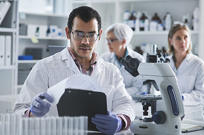 Buy stock photo Shot of a young scientist going through notes while working in a lab with his colleagues in the background