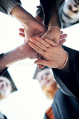 Buy stock photo Low angle shot of a group of students holding their hands together in a huddle on graduation day