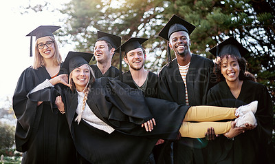 Buy stock photo Portrait of a group of students holding one of their peers on graduation day