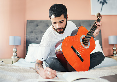 Buy stock photo Shot of a man writing in his notebook while playing the guitar at home