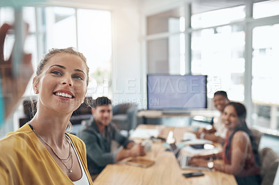 Buy stock photo Shot of a young businesswoman using a glass wall during a presentation to her colleagues in an office