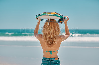 Buy stock photo Rearview shot of a young woman holding a surfboard over her head at the beach