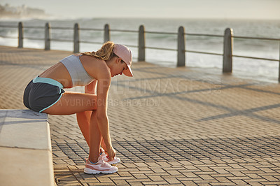 Buy stock photo Shot of a sporty young woman tying her laces while exercising along a promenade