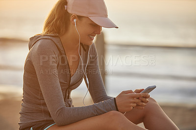 Buy stock photo Shot of a sporty young woman wearing earphones and using a cellphone while exercising outdoors
