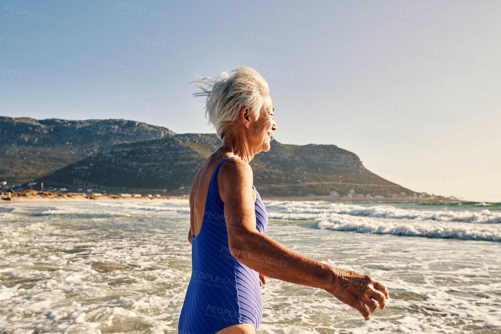 Buy stock photo Shot of a senior woman having fun in the water at the beach