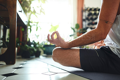 Buy stock photo Shot of an unrecognisable man meditating in the lotus position at home