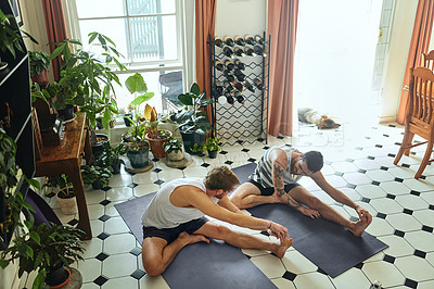 Buy stock photo Shot of two young men going through a yoga routine at home