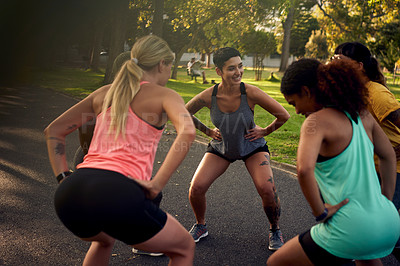 Buy stock photo Shot of a group of young women doing squats during their workout in a park