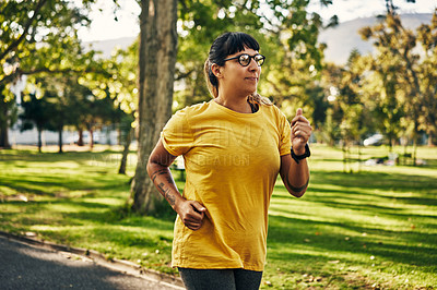 Buy stock photo Shot of a young woman going for a run in the park