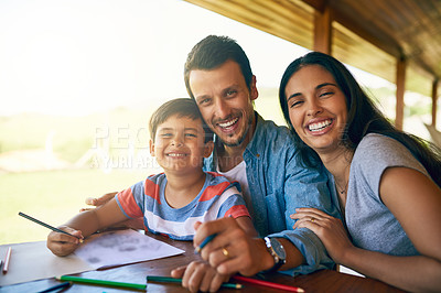 Buy stock photo Cropped shot of young affectionate parents colouring in pictures with their adorable son at home