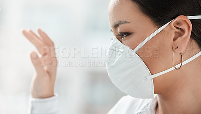 Buy stock photo Shot of a masked young businesswoman looking out of a window and waving in a modern office