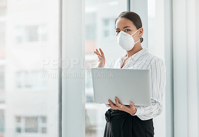 Buy stock photo Shot of a masked young businesswoman holding a laptop and waving out of a window in a modern office