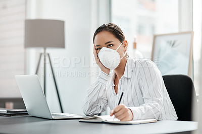 Buy stock photo Shot of a masked young businesswoman looking unhappy while working at her desk in a modern office