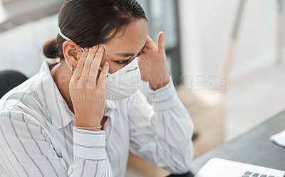 Buy stock photo Shot of a masked young businesswoman looking stressed while working at her desk in a modern office