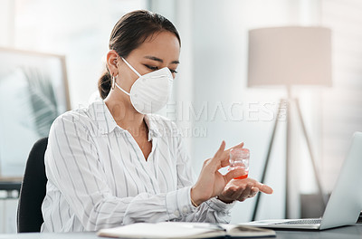 Buy stock photo Shot of a masked young businesswoman using hand sanitiser while working at her desk in a modern office