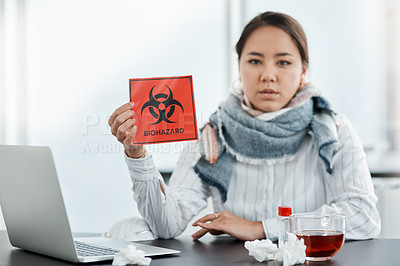 Buy stock photo Shot of a young businesswoman holding a biohazard sign at her desk in a modern office