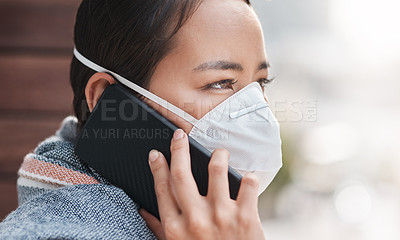 Buy stock photo Shot of a young woman wearing a mask while talking on the phone on the balcony at home