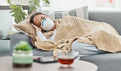 Buy stock photo Shot of a woman wearing a mask while lying sick at home