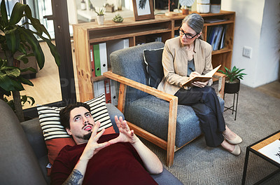 Buy stock photo Shot of a young man having a therapeutic session with a psychologist
