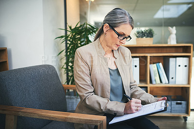 Buy stock photo Shot of a mature psychologist writing notes on a clipboard