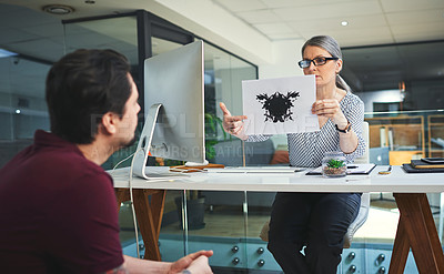 Buy stock photo Shot of a mature psychologist conducting an inkblot test with her patient during a therapeutic session