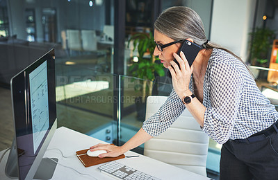 Buy stock photo Shot of a confident mature psychologist using a smartphone and computer in a modern office