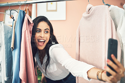 Buy stock photo Shot of a woman sticking her head in between items on a clothing rail while taking a selfie