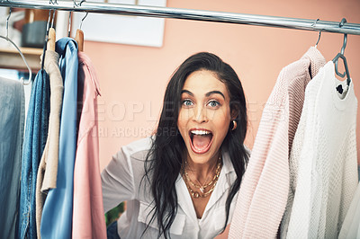 Buy stock photo Shot of a young woman sticking her head in between items on a clothing rail