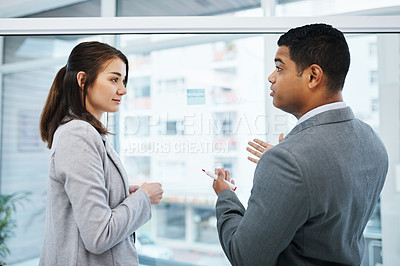 Buy stock photo Shot of a young businessman and businesswoman having a brainstorming session in a modern office