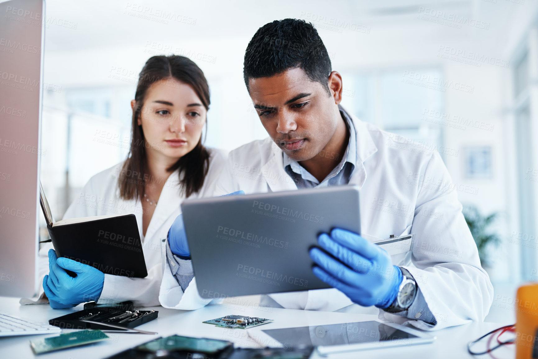 Buy stock photo Shot of a young man and woman using a digital tablet while repairing computer hardware in a laboratory