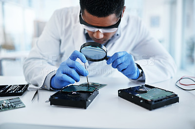 Buy stock photo Shot of a young man using a screwdriver and magnifying glass while repairing computer hardware in a laboratory