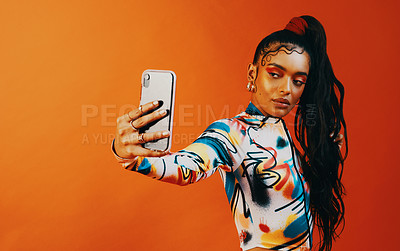 Buy stock photo Studio shot of a fashionable woman taking a selfie against a orange background
