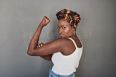 Buy stock photo Studio portrait of a young woman flexing her biceps against a grey background