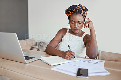 Buy stock photo Shot of a young woman writing notes while working from home