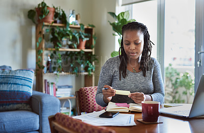 Buy stock photo Shot of a young woman making notes while working from home