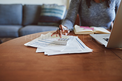 Buy stock photo Cropped shot of a woman going through paperwork while working from home