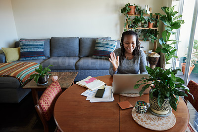 Buy stock photo Shot of a young woman using a laptop to have a web conference at home