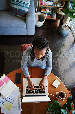 Buy stock photo High angle shot of a young woman using a laptop while working from home