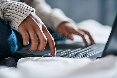 Buy stock photo Cropped shot of an unrecognisable man using a laptop on his bed at home