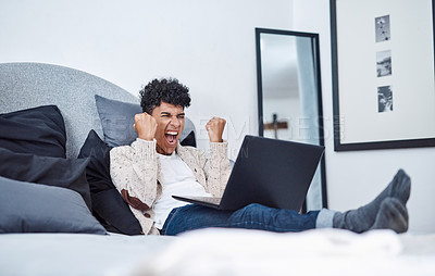 Buy stock photo Shot of a young man cheering while using a laptop on his bed at home
