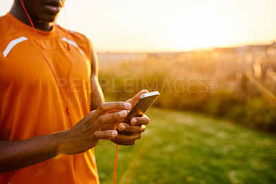 Buy stock photo Closeup shot of a sporty man using a cellphone while exercising outdoors