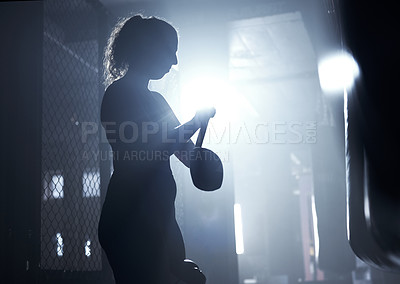 Buy stock photo Shot of a sporty young woman strapping her gloves while boxing in a gym