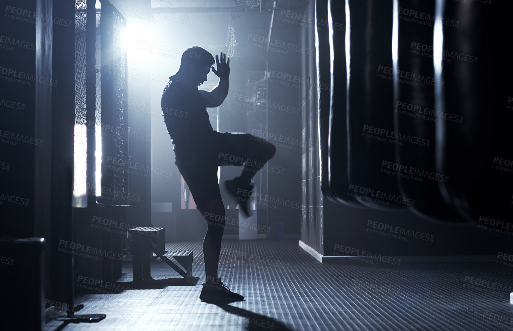 Buy stock photo Shot of a sporty young man kickboxing in a gym