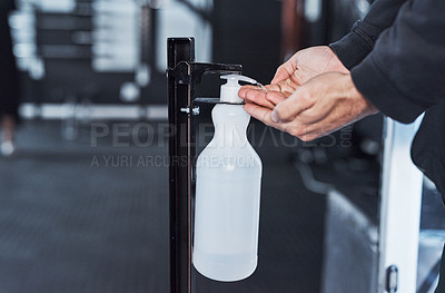 Buy stock photo Closeup shot of an unrecognisable man using a hand sanitiser dispenser in a gym