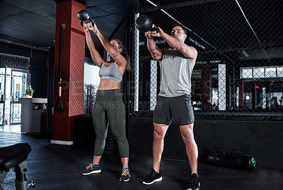 Buy stock photo Shot of two sporty young people exercising with kettlebells in a gym