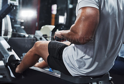 Buy stock photo Cropped shot of an unrecognizable male athlete working out on a rowing machine in the gym